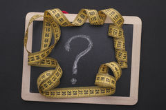 Measuring tape on blackboard with question mark Stock Images
