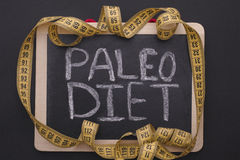 Measuring tape on blackboard with the words Paleo Diet Royalty Free Stock Photos