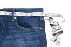 Measuring tape on blue jeans Stock Image