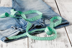 Measuring tape on blue jeans at waist Royalty Free Stock Image