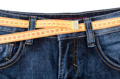 Measuring tape on blue jeans at waist isolated on white Royalty Free Stock Photography