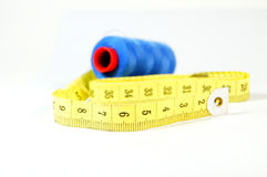 Measuring tape with blue threads. On white background Stock Photos