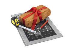 A measuring tape, brick and a pencil over a construction drawing Stock Images