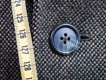 Measuring tape and buttoned button on tweed jacket Stock Photo