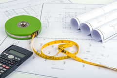 Measuring Tape and calculator on plan drawing Royalty Free Stock Images