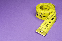Measuring Tape. Coiled Yellow Measuring Tape on Purple Background Photo Stock Image