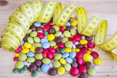 Measuring tape and colorful candy Royalty Free Stock Images