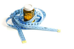 Measuring tape and container with tablets Stock Photography