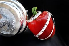 Measuring tape curl up on a Red Sweet Pepper with Silver Dumbbell. Diet concept,measuring tape curl up on a Red Sweet Pepper with Silver Dumbbell on black Stock Photo