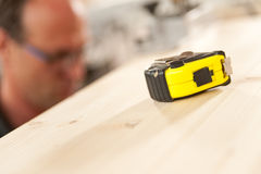 Measuring tape in focus in carpenter workshop Stock Images
