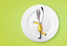 Measuring tape on a fork and knife Royalty Free Stock Image
