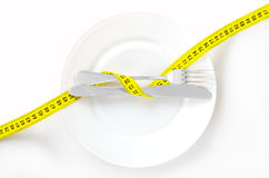 Measuring tape on a fork and knife - dieting concept image Stock Image