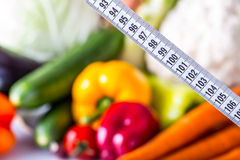 Measuring tape and Fresh vegetable and fruits in the background. Healthy diet  concept Royalty Free Stock Photography
