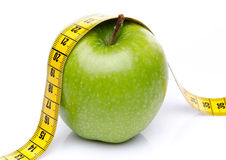 Measuring tape on a green apple Royalty Free Stock Photo