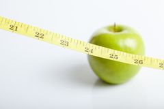 Measuring tape with green apple Royalty Free Stock Photo
