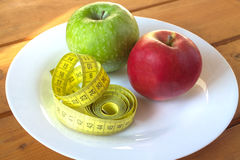 Measuring tape and green apples on plate Royalty Free Stock Photos
