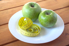 Measuring tape and green apples on plate Stock Photo
