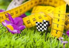 Measuring tape. In green grass with checker flag Stock Photos