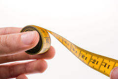 Measuring tape in hand. Hand holding a yellow measuring tape Stock Photography
