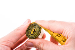 Measuring tape in hand. Hand holding a yellow measuring tape Royalty Free Stock Photos