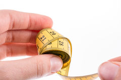 Measuring tape in hand. Hand holding a yellow measuring tape Stock Photo