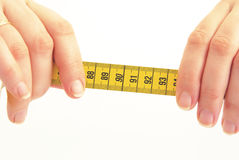 Measuring tape in the hands. Royalty Free Stock Images