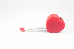 Measuring tape in heart shape on white background Stock Photos