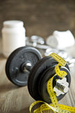 Measuring tape and iron dumbbell Stock Image