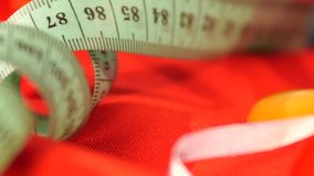 Measuring tape isolated on red cloth, close up stock video