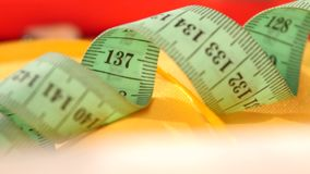 Measuring tape isolated on yellow cloth, close up stock video