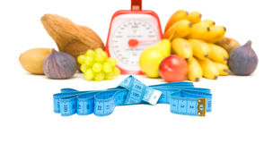 Measuring tape, kitchen scale and vegetables on a white backgrou Royalty Free Stock Images