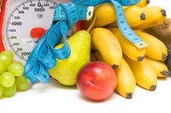 Measuring tape, kitchen scales and fresh fruit closeup. Royalty Free Stock Photography