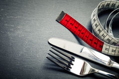 Measuring tape, knife and fork Stock Photos