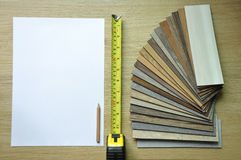 Measuring tape on laminate floor plank. Samples of laminate and vinyl floor tile on wooden Background Stock Photos
