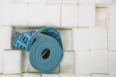 Measuring tape among lump sugar. Concept problem with excess weight royalty free stock photo