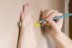 Measuring with tape measure on wall Stock Images