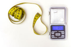 Measuring Tape and Medicine Scale. Measuring Tape and a Medicine Scale on a white background Royalty Free Stock Photo