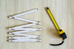 Measuring tape and meter on wooden background. Top view. Royalty Free Stock Photography
