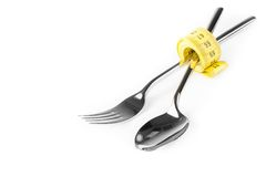 Measuring tape near spoon and fork, concept of nutrition and diet Royalty Free Stock Photo