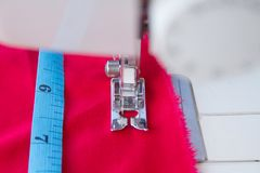 Measuring tape and needle of sewing machine Stock Photography