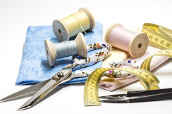 Measuring tape and other sewing tools. Scissors, threads and fabrics on white Stock Photo