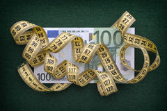 Measuring tape over one hundred euro note on green background Stock Photos