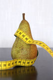 Measuring tape and pear Stock Photo