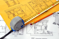 A measuring tape and a pencil on a floor plan blue Stock Image