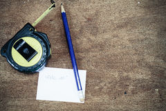 Measuring tape, pencil, white paper on vintage wooden background Stock Image
