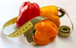 Measuring tape and pepper on a white background. Fitness stock images
