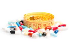Measuring tape with pills for dieting around Stock Photography
