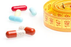 Measuring tape and pills for dieting Stock Images