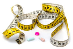 Measuring tape with pills Royalty Free Stock Photos