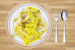 Measuring tape and plate with cutlery on table. Close up of silver cutlery with measuring tape in a plate on the wooden table Royalty Free Stock Images